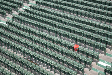 stadium of green chairs with one red chair